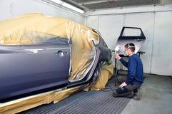 Trabajador que pinta un coche. Imagen de archivo libre de regalías
