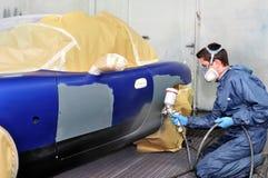 Trabajador que pinta un coche. Foto de archivo