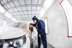 trabajador que pinta un coche blanco en garaje especial, traje que lleva y engranaje protector Imagenes de archivo