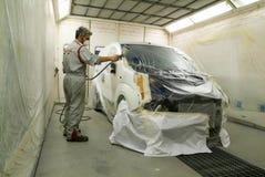 Trabajador que pinta un coche en su garaje Fotos de archivo libres de regalías