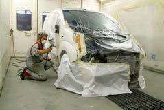 Trabajador que pinta un coche en su garaje Imagenes de archivo