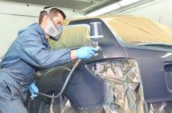 Trabajador que pinta un coche gris Fotos de archivo