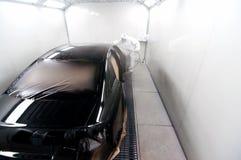 Trabajador que pinta un coche negro en una cabina especial Imagenes de archivo
