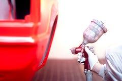 Trabajador que pinta un coche o un elemento rojo en garaje Imagen de archivo libre de regalías
