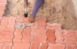 Trabajador que pone bloques de pavimentación concretos rojos fotografía de archivo