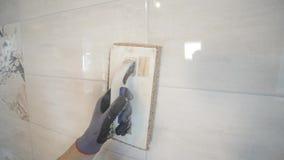 Trabajador que pone la fuga en la pared en la cocina Mampostería de la teja almacen de video