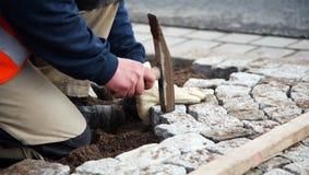 Trabajador que pone piedras de pavimentación Fotografía de archivo libre de regalías