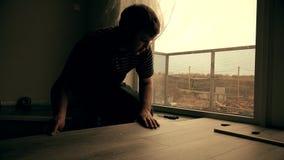 Trabajador que pone un piso con los tableros de suelo laminados metrajes