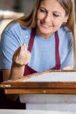 Trabajador que quita fibras grandes del papel con Foto de archivo