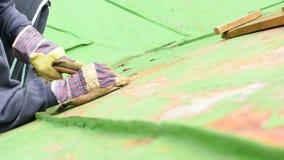 Trabajador que raspa de la pintura verde almacen de video