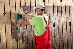 Trabajador que raspa la pintura agrietada vieja de la cerca de madera con el poder t Fotografía de archivo libre de regalías