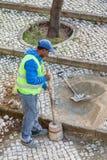 Trabajador que repara el pavimento de la acera con el hecho a mano tradicional y típico Imágenes de archivo libres de regalías