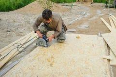 Trabajador que repara en una casa de campo Foto de archivo