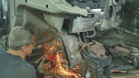 Trabajador que repara a la carrocería en garaje almacen de video