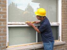 Trabajador que repara una ventana Fotos de archivo libres de regalías