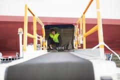 Trabajador que se agacha en aeroplano con el transportador del equipaje en primero plano Fotos de archivo libres de regalías