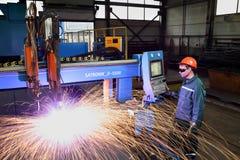 Trabajador que se coloca cerca del cutt del metal del plasma del panel de control de la máquina Foto de archivo