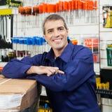 Trabajador que se inclina en el paquete de la herramienta en tienda del hardware Fotos de archivo libres de regalías