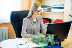 Trabajador que se sienta delante del ordenador portátil Fotos de archivo libres de regalías