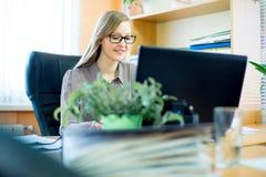 Trabajador que se sienta delante del ordenador portátil Fotos de archivo