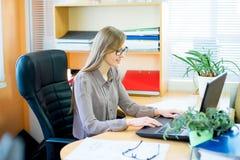 Trabajador que se sienta delante del ordenador portátil Foto de archivo libre de regalías