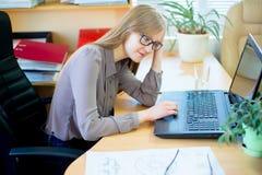 Trabajador que se sienta delante del ordenador portátil Fotografía de archivo