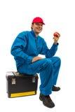 Trabajador que se sienta en la caja de herramientas con la manzana roja a disposición imagenes de archivo