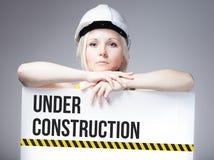 Trabajador que se sostiene bajo muestra de la construcción en tablero de la información Foto de archivo libre de regalías