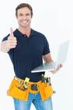 Trabajador que sostiene el ordenador portátil mientras que gesticula los pulgares para arriba Imagen de archivo libre de regalías
