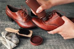 Trabajador que sostiene el zapato y que aplica al limpiabotas del zapato Foto de archivo