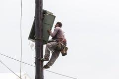 Trabajador que sube en línea de transmisión concreta eléctrica del polo Fotos de archivo