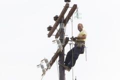 Trabajador que sube en línea de transmisión concreta eléctrica del polo Foto de archivo libre de regalías