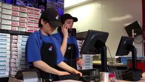 Trabajador que toma la llamada de teléfono para la pizza del dominó del cliente que ordena