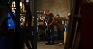 Trabajador que trabaja con el tubo en el taller 4k de la fundición almacen de video