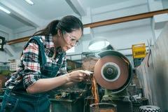Trabajador que trabaja a máquina que muele que usa la herramienta de la rueda abrasiva Foto de archivo libre de regalías