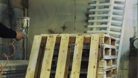 Trabajador que usa el aerógrafo para pintar la plataforma de madera blanca en el taller almacen de metraje de vídeo