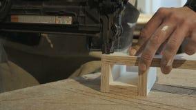 Trabajador que usa el arma de la grapa para fijar las piezas de madera metrajes