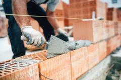 trabajador que usa el cuchillo de la cacerola para las paredes de ladrillo constructivas con el cemento y el mortero imagen de archivo libre de regalías