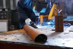 Trabajador que usa el equipo de soldadura para la metalurgia fotografía de archivo