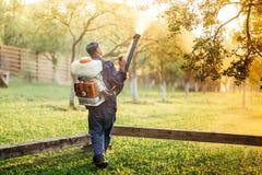 trabajador que usa el rociador para la distribución orgánica del pesticida en huerta de fruta foto de archivo