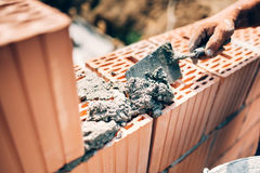 Trabajador que usa la paleta y las herramientas para construir las paredes exteriores con los ladrillos y el mortero imágenes de archivo libres de regalías