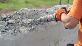 Trabajador que usa la perforadora concreta Un hombre sacude la pared con una desviación metrajes