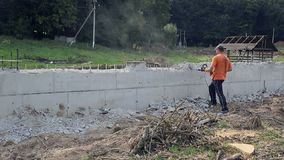 Trabajador que usa la perforadora concreta Un hombre sacude la pared con una desviación almacen de video