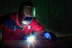 Trabajador que usa la rueda eléctrica que muele en el acero Fotos de archivo