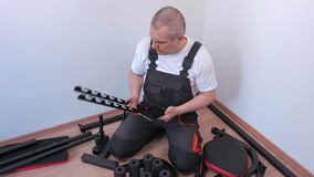 Trabajador que usa la tableta cerca de componentes de la máquina del ejercicio metrajes