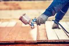trabajador que usa los guantes protectores que pintan la madera de madera con el arma de la pintura de espray Fotografía de archivo