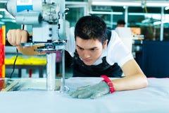 Trabajador que usa una máquina en fábrica china imagen de archivo