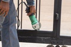 Trabajador que usa una amoladora de ángulo a los marcos de puerta de pulido Fotos de archivo libres de regalías
