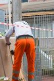 Trabajador que usa una amoladora orbital en la naranja que lleva superficial de acero imagenes de archivo