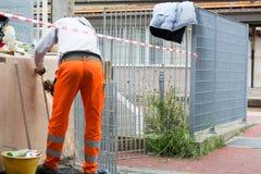 Trabajador que usa una amoladora orbital en la naranja que lleva superficial de acero fotos de archivo